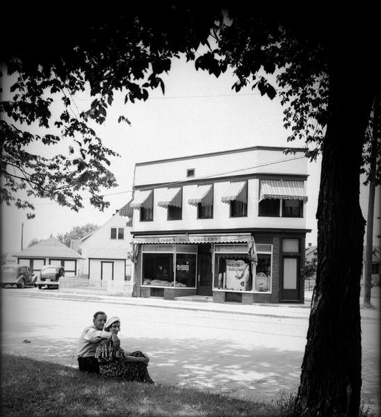 "Linden Hill Grocery Store, 36 South Fair Oaks Avenue. Anton ""Tony"" Lazarz and his wife Bernice, owners of the store, are sitting on the curb in the foreground, which is across the street from the store."