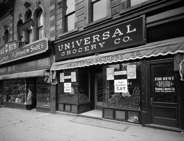 "Storefront of the Universal Grocery Company at 20 W. Mifflin Street, with window displays. On the left is a portion of The Hub, 22 W. Mifflin Street, a store for men's clothes and Florsheim Shoes. On the right is a doorway with a sign that reads: ""For Rent, Entire Second Floor, Stanley C. Hanks, Co."""