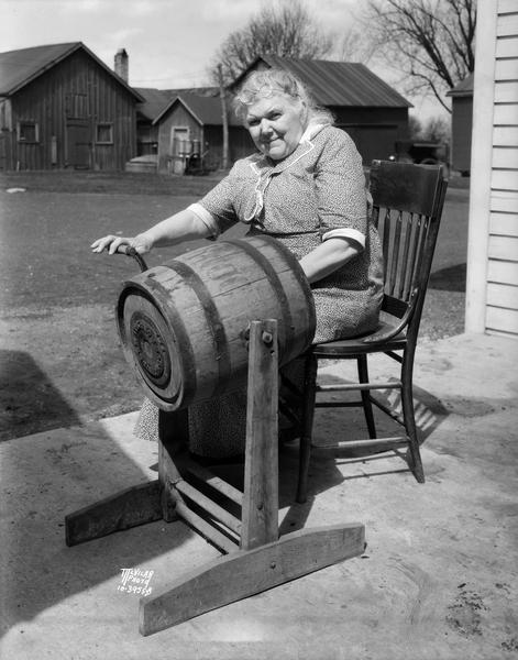 Ellen (Mrs. William) Lacy, of Sunny Slope farm, 5810 Lacy Road, south of Madison, sitting in the farmyard and turning a barrel butter churn.