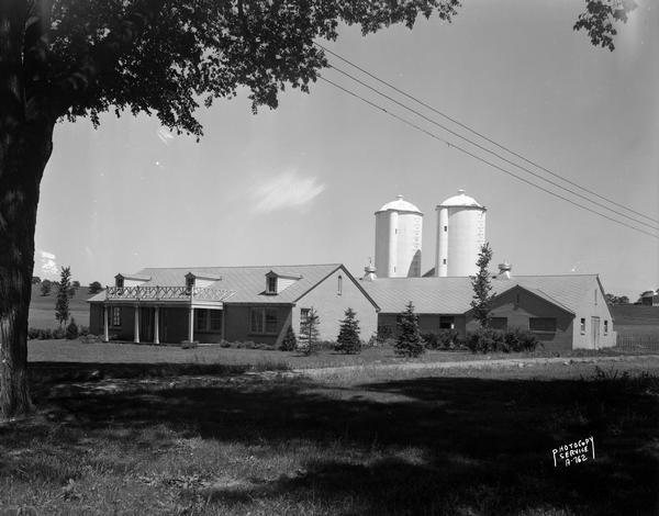 Rennebohm dairy farm buildings, showing house in foreground and barn and silos in background, framed by large tree, located 5 miles from the capitol on Highway 151 between Madison and Sun Prairie. The milk produced on the farm was used in the Rennebohm soda fountains.
