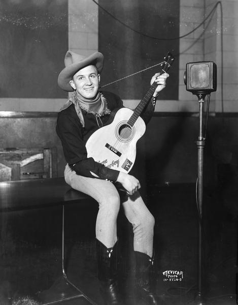A man dressed as a cowboy is sitting and holding a guitar in front of a microphone in W.I.B.A. studios, 111 King Street, Room 28.