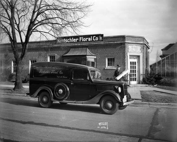 Man holding long stem rose box beside Rentschler Floral Co. delivery truck. He is parked in front of Rentschler greenhouse office building, located at 2500 Regent Street.