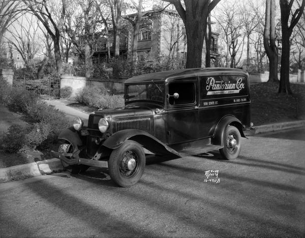 Delivery truck for Pantorium Cleaners, 558 State Street, with Hanks mansion, located at 525 Wisconsin Avenue, in the background among trees.