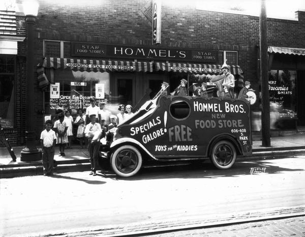 "Hommels Star Food Store at 606 S. Park Street, with promotional truck in front of store, and children looking on. Vehicle has a painted sign on the side: ""Hommel Bros. new food store, specials galore! Free toys for the kiddies."" There is a man dressed as a clown playing an instrument, and there are cardboard cutouts of other musicians."