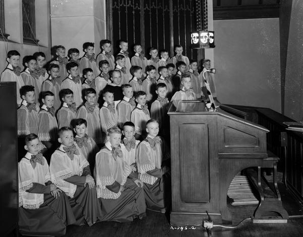 Blessed Sacrament Catholic Church's boys choir grouped in front of the organ, with The Reverend James A. McInerney (Father Mac) in their midst. The church is located at 2119 Rowley Avenue.