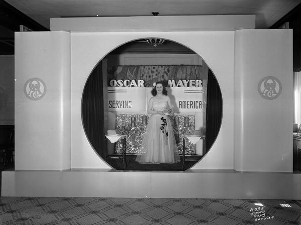 "A female model standing and wearing a long dress on the ""Oscar Mayer Serving America"" stage set, holding a meat product."