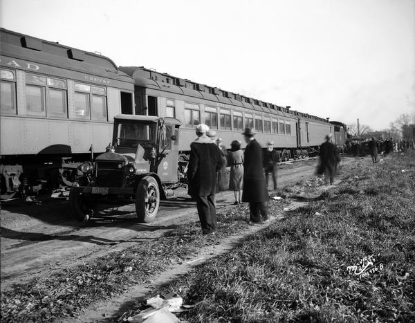 People looking at the train cars and undamaged front end of the Wisconsin Telephone Company truck involved in the Milwaukee Road passenger train-truck accident.