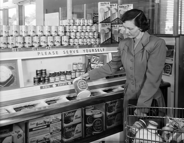 "Woman grocery shopper with shopping cart selecting ""Lady Borden"" ice cream from freezer below shelves of related food items."
