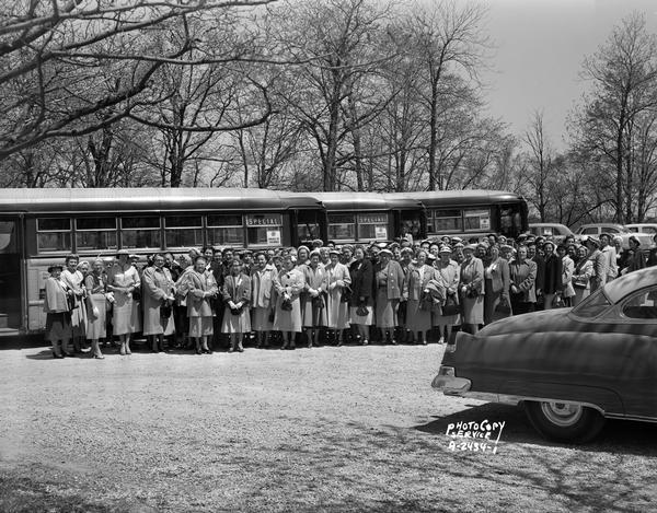 Large group of Knights of Columbus women, standing in front of buses made to look like railroad cars. They are returning from a convention held in Racine.