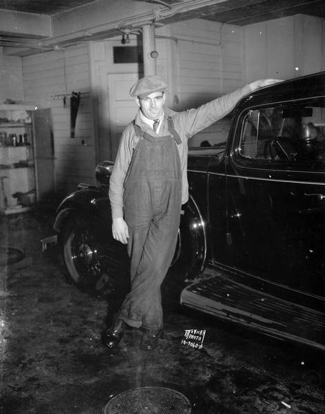 Governor La Follette's new chauffeur, Steve Tschida, in the garage standing next to the car.