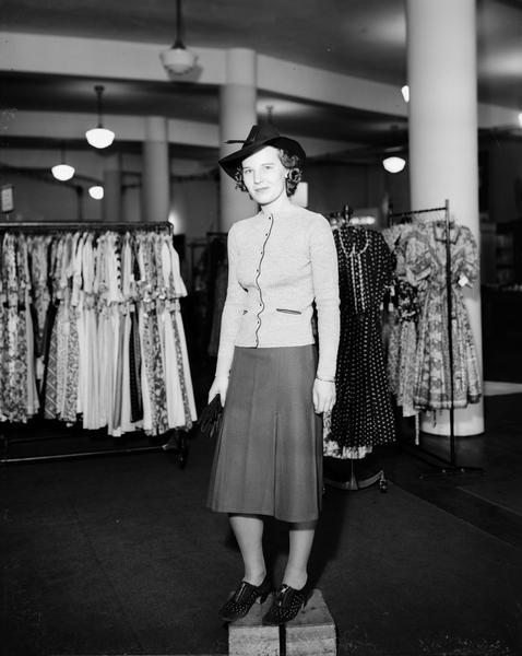 Model standing on box wearing jacket and skirt, hat, carrying gloves. Part of a fashion series from Kessenich's Ready to Wear, 201-203 State Street, with racks of dresses.