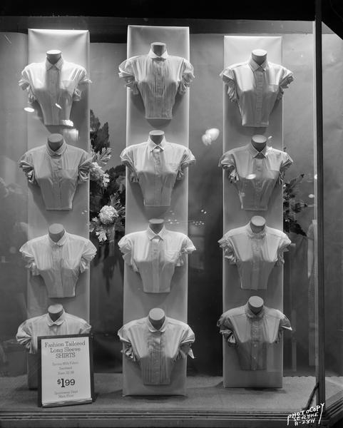 "Exterior night view night of Hill's Department Store window, 202 State Street, displaying twelve ladies' ""fashion tailored"" long sleeve shirts.  Advertised for sale for $1.99."