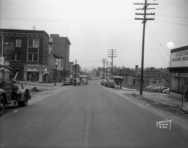 View down middle of East Wilson Street at the center of South Hancock looking Northeast, taken at site of Reynolds Bus accident. Businesses shown include Dizon Men's Clothing at 402 East Wilson Street, Krehl's Drugstore at 408 East Wilson Street, the Cardinal Hotel at 416-18 East Wilson Street, the Milwaukee Road Franklin Street station at 501 East Wilson Street, and Electric Motor Service at 323 East Wilson Street.