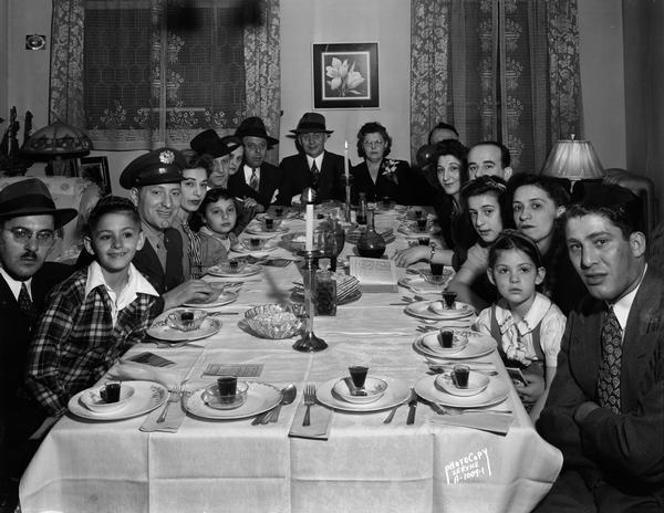 Close-up group portrait of Abe and Sarah Mintz's family gathered around the dining room table for Passover supper, 336 West Wilson Street.