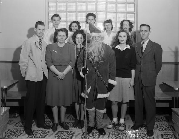 Group portrait of ten employees of the Rennebohm's drugstore #12 at  2526 Monroe Street, posed at a Christmas party with Santa Claus.