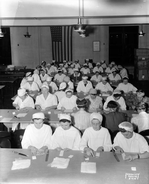 Large group of Red Cross Workers seated at tables, preparing surgical dressings in the assembly room at the American Federation of State, County and Local Employees Building, 448 West Washington Avenue.