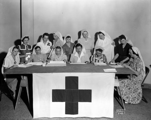 State female employees making surgical dressings / bandages for the American Red Cross in the Wisconsin State Employees Association building, 448 W. Washington Avenue. Seated, l to r: Marion Block, Lenore Hassett, Caroline Dagestad, Lydia Stumpf (leader), Vyrgil Tuft, and Dorothy Ryan. Standing, l to r : Lenore Brownlee, Rosaline Bee, Eulalia Fader, Eleanor DeMerse, Rosella Marshall, Zenobia Peachey and Dorothy Wilhelm.
