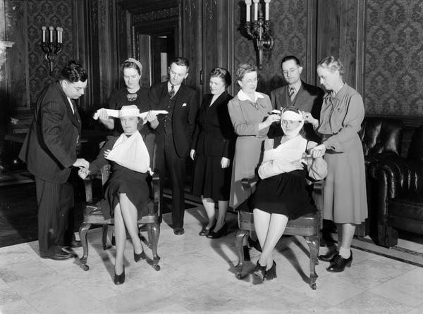 Red Cross first aid class of State government employees in the Wisconsin State Capitol Assembly parlor practicing bandaging - standing l to r: E.C. Giessel, Budget Bureau; Margaret Miller, instructor; W.C. Graham, Highway Commission; Catherine Collins, Tax Commission; Esther Schadde, instructor, Board of Health; G.M. Mathews, Banking Commission; and Marion Poole, instructor, Highway Commission. The victims are Audrey Hett (left) Bureau of Personnel and Ruth Heise, Board of Health.