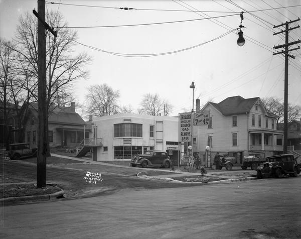 View from street towards two men filling the gas tanks of a car and truck at Jack D. Taylor's Super Service Station, 751-753 Williamson Street. This Art Deco style building is located at the corner of Williamson and Livingston Street.