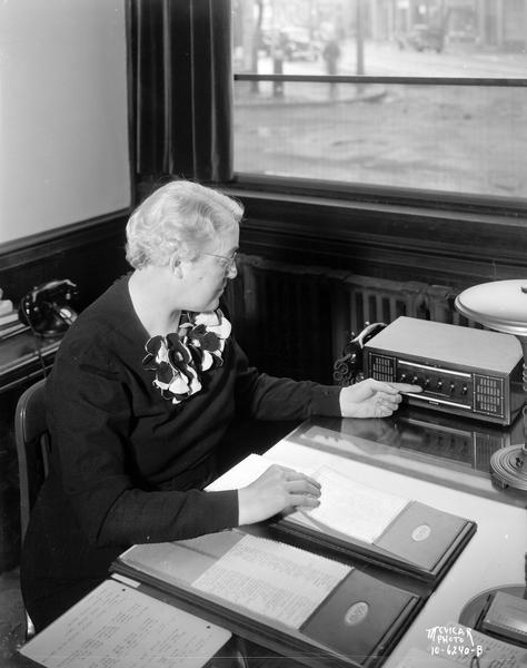 Regina Groves (Mrs. Earl Barnhart), sitting at her desk, operating an interdepartment communication system at the Groves School for Secretaries. Behind her is a window that looks out onto the street.