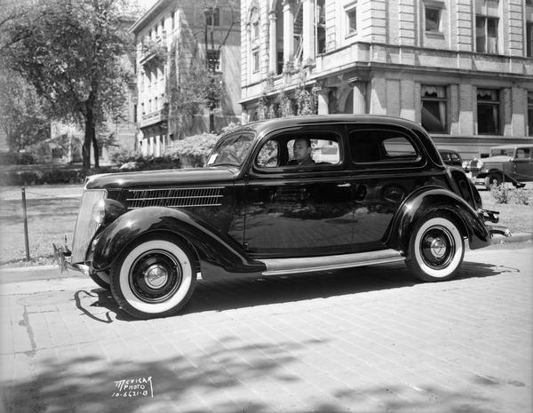Harry Stuhldreher, University of Wisconsin-Madison head football coach, sitting in new Ford car in front of U.W. YMCA building, 740 Langdon Street.