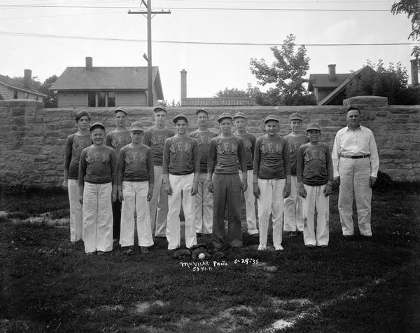 Group portrait of twelve boys on the V.F.W. baseball team in uniform, with the male coach standing on the right.