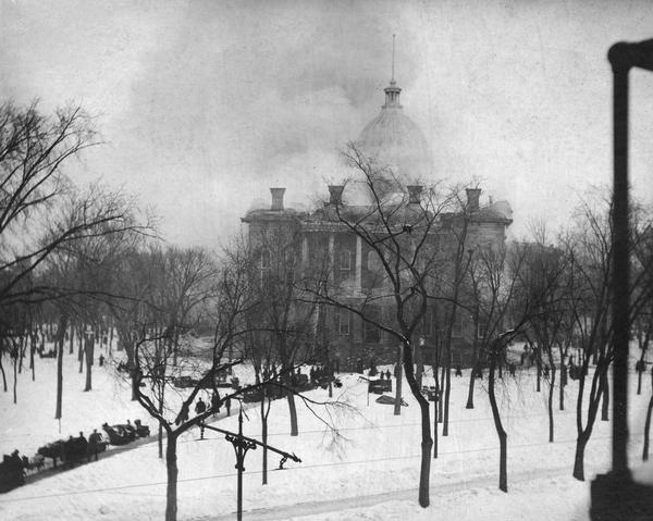 Fire at the third Wisconsin State Capitol, showing the South Wing, and spectators gathered on the path. Some of the salvaged contents of the building are scattered on the snow.
