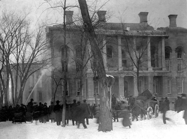 Wisconsin State Capitol fire, showing a crowd watching near the South Wing. Some of the contents of the building are already in wagons ready to be hauled away.