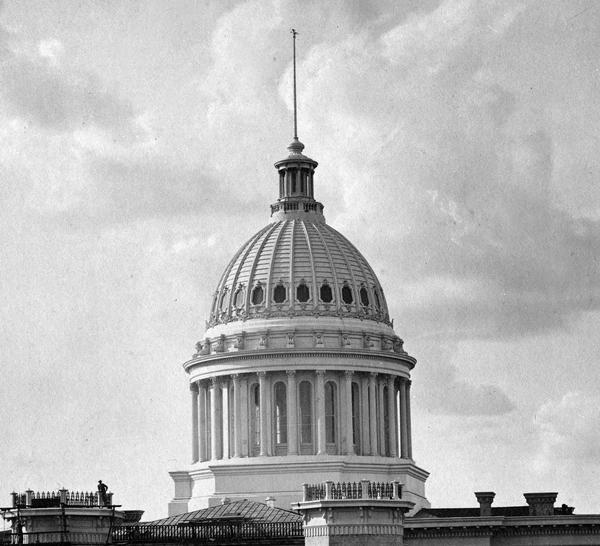 The dome of the third Wisconsin State Capitol, which was constructed entirely of iron and glass, as it appeared in 1878. The dome was painted white which some contemporary observers felt did not blend well with the buff colored Prairie du Chien sandstone of the rest of the building.