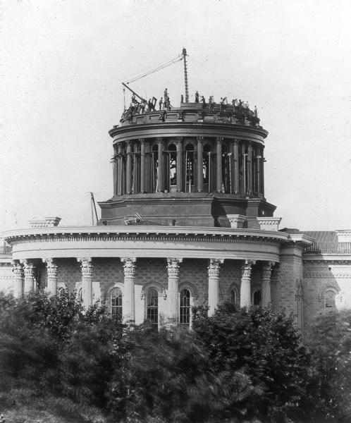 The second Wisconsin State Capitol dome under construction, showing the workmen and the equipment they used to hoist construction materials into place.