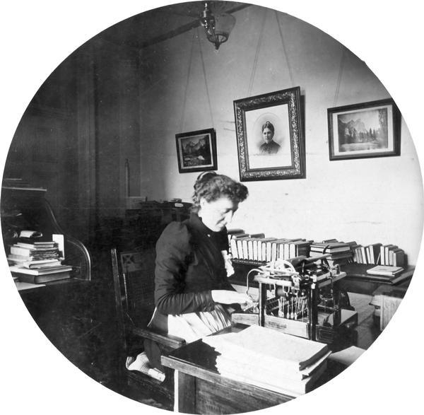 Minnie Oakley, assistant librarian of the Wisconsin Historical Society, seated at her desk in the South Wing of the Wisconsin State Capitol.  This photograph, combined with a similar portrait of Emma Hawley, suggests that librarians included aprons in their work wardrobes.  This round portrait was taken by Reuben Gold Thwaites, secretary of the Historical Society and an avid amateur photographer, using the popular Kodak 2 format.