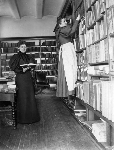 Minnie Oakley and Florence Baker Hayes (reaching for a book), two Historical Society librarians, during the period when the Society was housed in the South Wing of the Wisconsin State Capitol. Details of the Capitol furnishing and construction in this photograph include the leather swivel chair (in need of repair) and the Jenny Lind table, as well as documentation of the ceiling construction.