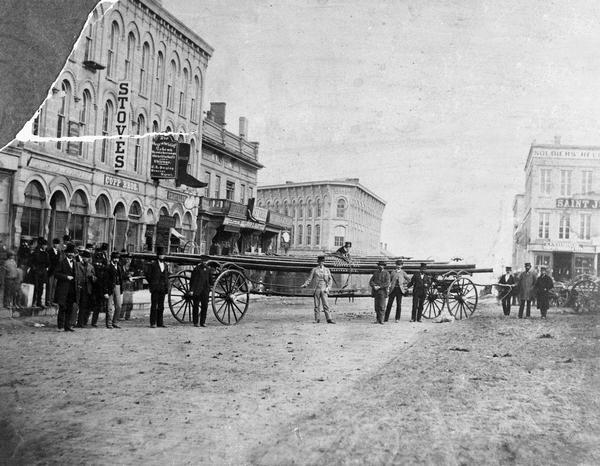 The first ladder wagon of Capitol Hook and Ladder Company #1 posed at the corner of Pinckney and Main streets to show off the length of the wagon and the 48-foot ladders. Four men were required to push this wagon to a fire. Capitol Hook & Ladder was a volunteer company formed in 1857. Until 1885, it was independent, and it purchased its own equipment.