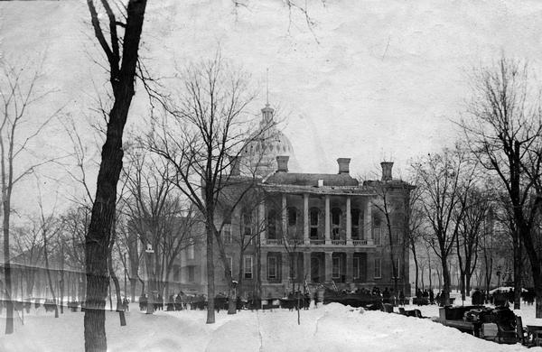 Spectators standing at the South Wing during the aftermath of the fire which destroyed the second Wisconsin State Capitol in Madison, February 26-27, 1904. Although the fire appears to be out in this photograph, smoke still obscures the dome. The pathways are littered with tables and chairs and books that have been rescued.