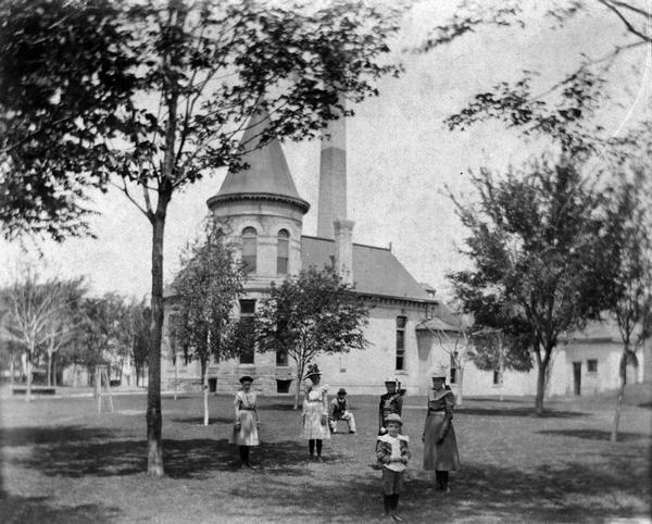 The Madison City Water Works pumping station at the intersection of Gorham and Livingston which provided pressure to the city's mains. A group of people stand on the lawn in the foreground.