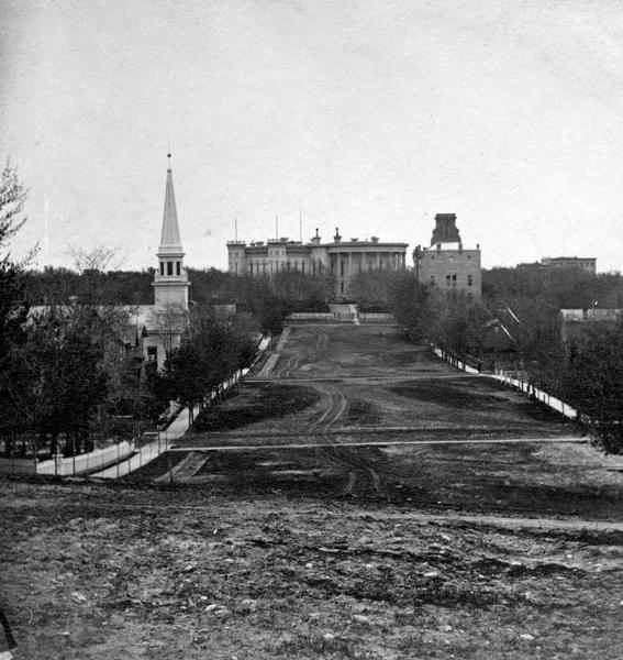 View from unpaved Wisconsin Avenue looking east toward the third Wisconsin State Capitol sometime prior to the completion of the dome (1869). The portion of the building seen here was designed by August Kutzbock and Samuel H. Donnel. Their dome was rejected, however, and Stephen V. Shipman designed the dome that was constructed.