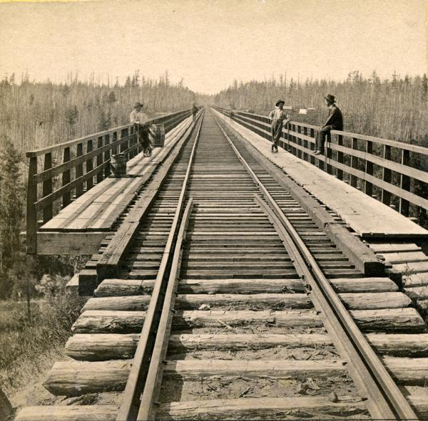 Stereograph of the view down the railroad tracks, with two men standing and one man sitting on the railing of the White River bridge, six miles south of Ashland. This bridge was part of the Wisconsin Central Railroad line, and was 1600 feet long and 110 feet above the water, making it one of the largest trestle bridges of its day.