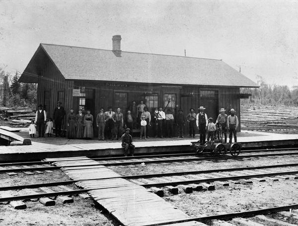 Elevated view across railroad tracks of the Wisconsin Central Railroad depot. Virtually the entire population of Sherry is thought to be standing on the platform for this photograph. A boy is standing on a handcar in the foreground. At Sherry, passengers on the Wisconsin Central could make connections to the backwoods on logging trains.