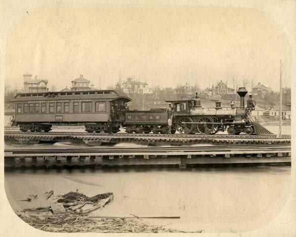 View across water of a Milwaukee, Lake Shore, and Western Railroad locomotive (No #33) pulling a pay car across a trestle over the Fox River. Several large homes are on a hill in the background.