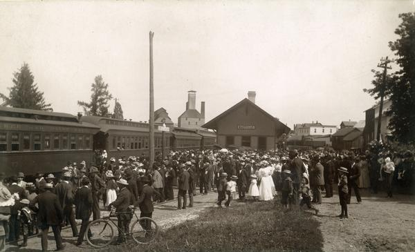 A large crowd at the Milwaukee Road depot, perhaps to greet William Jennings Bryan on the incoming train. The malthouse can be seen in the distance.