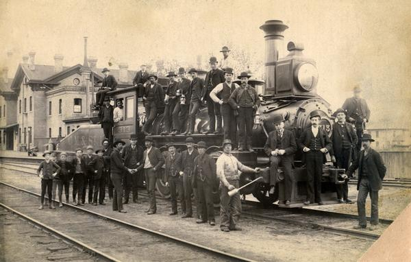A group of men and boys posed around Chicago, Milwaukee & St. Paul Railway locomotive # 313, a switch engine. The Fox House is in the background.