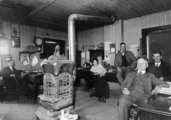 Employees of the Chicago, Milwaukee & St. Paul Railway in the company's Waukesha office.  Left to right they are Carl Mix, Ruth McGeen, Clarence Mica (seated on the table), Tom Taylor (seated in the chair), and John Lawless.  The room is heated by a large stove in the center of the room.