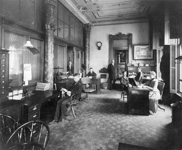 General office of the Chicago, Milwaukee, and St. Paul Railway Company in the Mitchell Building in Milwaukee. Left to right: the individual seated in left foreground is unknown; standing, William Kenally; seated, unknown; standing in doorway, D.W. Keyes; seated, O.F. Bird; seated, David Harlowe; and seated, Mary Miller.