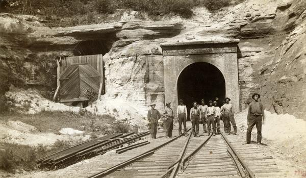 View down railroad tracks towards a group of construction workers posed near the east portal of the railroad tunnel near Tunnel City.