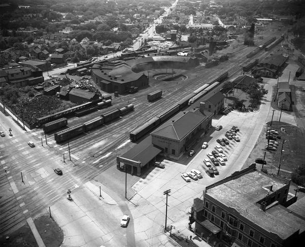 Aerial view of the Chicago, Milwaukee, and St. Paul Railroad station, roundhouse, and yard at the intersection of West Washington Avenue (across lower left corner) and Regent Street (angled mid-left to top).