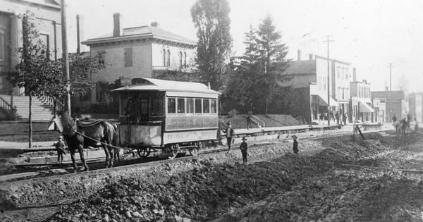 View across road construction towards a horse-drawn trolley on railroad tracks on Racine Street. Men and children are standing near piles of road building materials near the trolley.
