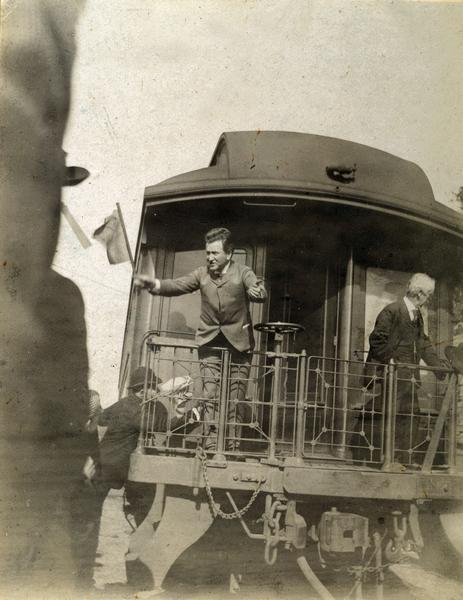 Robert M. La Follette, Sr., waving a flag from the back of a train as he campaigns for governor.