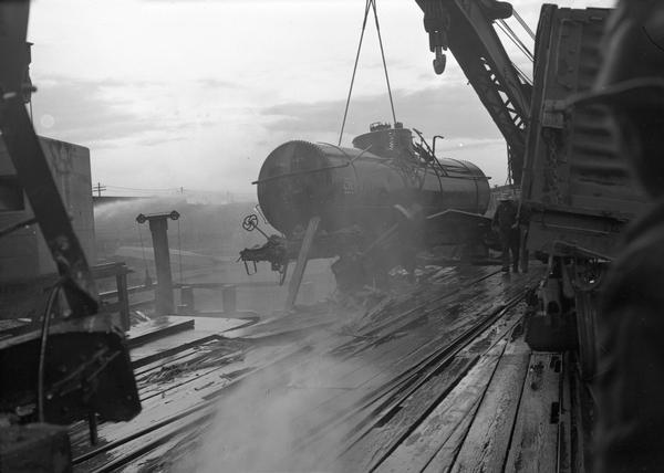 Tank car wreck at the Grand Trunk Western Railroad car ferry docks. A man wearing a hat is in the right foreground.