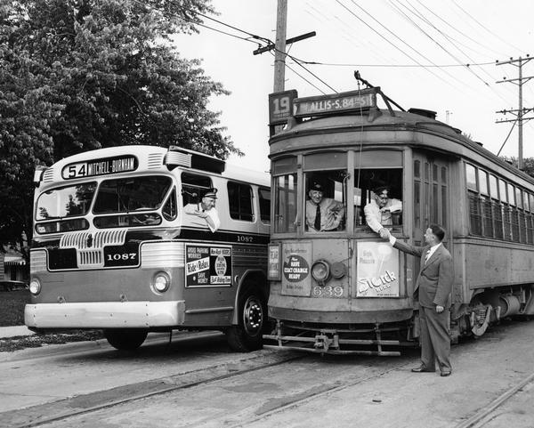 A posed photograph taken for the Milwaukee & Suburban Transport Corp. to mark the substitution of buses for streetcars on the West Burnham Street line.