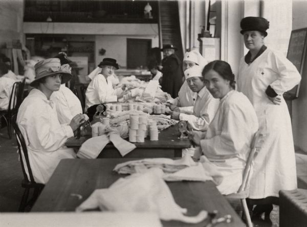 Red Cross volunteers preparing bandages at a Red Cross office in New York City. The woman standing on the right, who is supervising the work, is Mrs. Belmont Tiffany. The photograph is undated but the original caption indicates that it was taken before the American declaration of war.